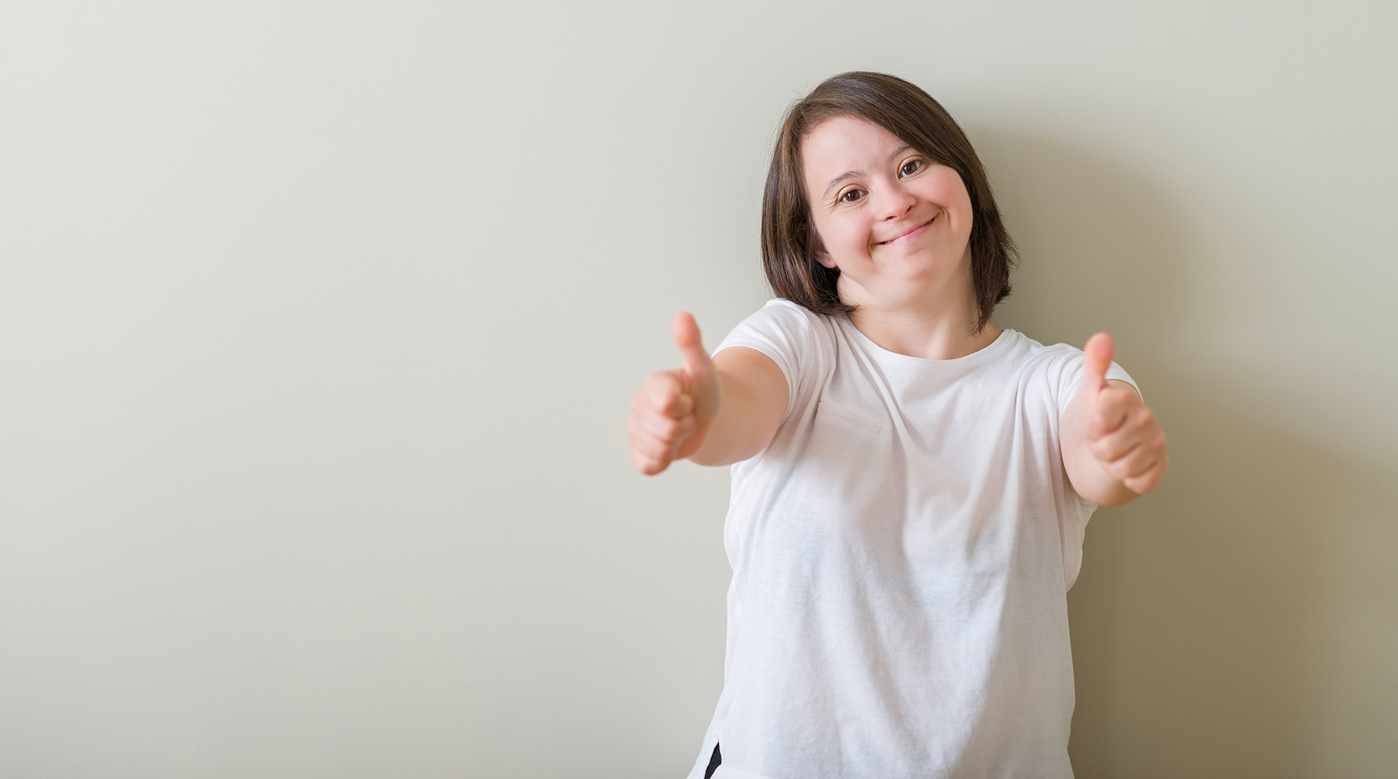 Down syndrome woman standing over wall approving doing positive gesture with hand, thumbs up smiling and happy for success. Looking at the camera, winner gesture.